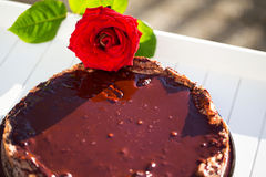 Backen Sie brwon Schokoladenkuchen mit einer roten Rose Stockbild