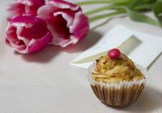 Backen Sie, der Buchstabe und der Blumenstrauß von Tulpen auf einer Tabelle als Geschenk zusammen lizenzfreie stockfotos