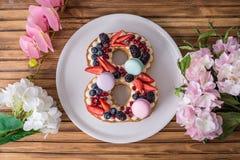 Backen Sie in Form von der Nr. zusammen 8, die mit Beeren und Blumen verziert wird Nachtisch für Frauen \ 's-Tag auf März achter Lizenzfreie Stockbilder