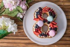 Backen Sie in Form von der Nr. zusammen 8, die mit Beeren und Blumen verziert wird Nachtisch für Frauen \ 's-Tag auf März achter Lizenzfreies Stockbild