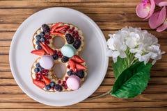 Backen Sie in Form von der Nr. zusammen 8, die mit Beeren und Blumen verziert wird Nachtisch für Frauen \ 's-Tag auf März achter Stockfotografie