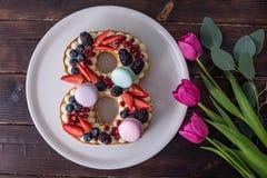 Backen Sie in Form von der Nr. zusammen 8, die mit Beeren verziert wird und blüht Tulpen Nachtisch für Frauen \ 's-Tag auf März a Stockfotos