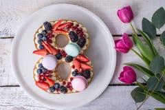 Backen Sie in Form von der Nr. zusammen 8, die mit Beeren verziert wird und blüht Tulpen Nachtisch für Frauen \ 's-Tag auf März a Lizenzfreies Stockbild