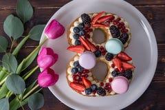 Backen Sie in Form von der Nr. zusammen 8, die mit Beeren verziert wird und blüht Tulpen Nachtisch für Frauen \ 's-Tag auf März a Stockfotografie