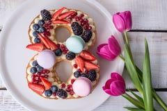 Backen Sie in Form von der Nr. zusammen 8, die mit Beeren verziert wird und blüht Tulpen Nachtisch für Frauen \ 's-Tag auf März a Stockbilder