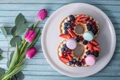 Backen Sie in Form von der Nr. zusammen 8, die mit Beeren verziert wird und blüht Tulpen Nachtisch für Frauen \ 's-Tag auf März a Lizenzfreie Stockfotos