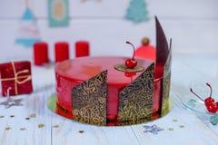 Backen Sie mit rotem Glasurspiegel mit Kirsch- und Schokoladendekoration zusammen Lizenzfreie Stockfotos