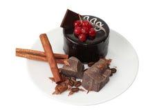 Backen Sie mit Zimt und Stücken dunkler Schokolade auf weißer Platte zusammen Lizenzfreies Stockfoto