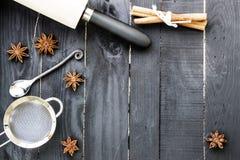 Backenbestandteile auf dem schwarzen rustikalen hölzernen Hintergrund Küchenwerkzeuge, -nüsse und -gewürze auf dem Holztisch Stockbilder