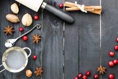 Backenbestandteile auf dem schwarzen rustikalen hölzernen Hintergrund Küchenwerkzeuge, -nüsse und -gewürze auf dem Holztisch Abbi Lizenzfreies Stockfoto