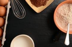 Backenbestandteile auf einer Steintabelle: Eier, Mehl, Zucker und Kakao Lizenzfreie Stockfotos