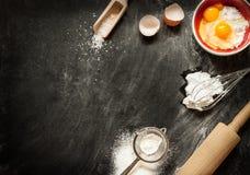 Backende Kuchenbestandteile auf Schwarzem von oben Lizenzfreies Stockfoto
