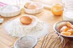 Backender Kuchen in der Küche - Teigrezeptbestandteile mit Frucht auf hölzerner Tabelle Stockbilder
