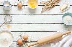 Backender Kuchen in der rustikalen Küche - Teigrezeptbestandteile auf weißem Holztisch Lizenzfreie Stockbilder