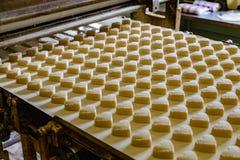 Backenfertigungsstraße Rohe ungekochte Plätzchen in der Form von Herzen nach der Formung des Gehens zum Ofen durch Förderer stockfotografie