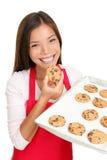 Backenfrau, welche die Plätzchen glücklich isst Stockfotos