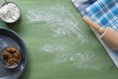 Backengeräte, Mehl, Zucker, Butter auf grüner Holzoberfläche Lizenzfreies Stockfoto