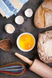 Backenhintergrund mit Brot, Eierschale, Mehl, Nudelholz Lizenzfreie Stockbilder