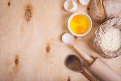 Backenhintergrund mit Brot, Eierschale, Mehl, Nudelholz clos Stockfotografie