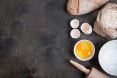 Backenhintergrund mit Eierschale, Brot, Mehl, Nudelholz Lizenzfreie Stockfotografie