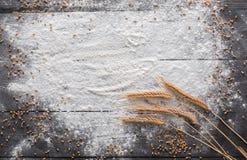 Backenkonzept auf hölzernem Hintergrund, besprühtes Mehl mit Kopienraum Stockfoto