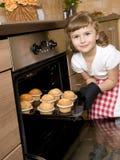 Backenmuffins des kleinen Mädchens Stockfotos
