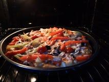 Backenpizza im elektrischen Ofen lizenzfreie stockbilder