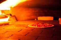 Backenpizza im Ofen mit brennendem Feuer Stockfotografie