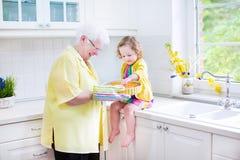 Backentorte der Großmutter und des kleinen Mädchens in der weißen Küche Lizenzfreie Stockfotos