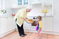 Backentorte der Großmutter und des kleinen Mädchens in der weißen Küche Stockbilder