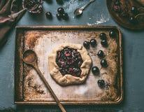 Backenvorbereitung der selbst gemachten offenen Kirschetorte oder des galette auf gealtertem Backblechhintergrund mit hölzernem L Stockfotografie
