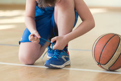 A backetball player. Lacing shoes Royalty Free Stock Photos