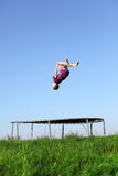 Backflip. Young boy doing a backflip on a trampoline on green meadow stock images