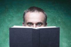 书被聚焦和钩的成熟人,读开放书,使年轻人,看起来封口盖板,绿色backg的惊人的眼睛惊奇 库存图片