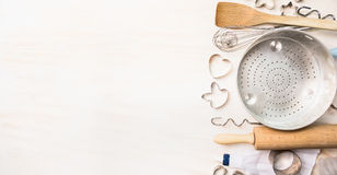 各种各样烘烤复活节依托的工具选择与饼干或曲奇饼在白色木backg的切削刀以兔宝宝的形式和心脏 图库摄影