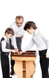 Backgammon. Two little boys and their father playing backgammon Stock Image