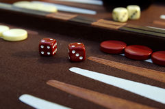 Backgammon 3. A wooden backgammon board showing dice that has rolled double twos and another set in the background rolling double ones Stock Photo