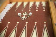 Backgammon bone square white dice for gambling with blurred background Stock Images
