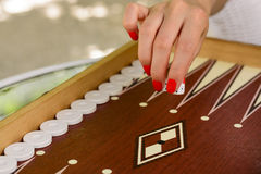 Backgammon bone square white dice for gambling with blurred background. woman with red nails is playing backgammon Royalty Free Stock Photo