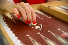 Backgammon bone square white dice for gambling with blurred background. woman with red nails is playing backgammon Royalty Free Stock Photography