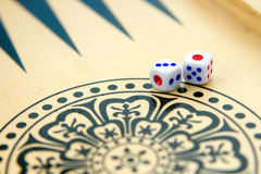 Backgammon Dice. Closeup two dice setup on backgammon wood board Royalty Free Stock Images