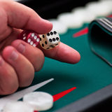 Backgammon player's hand holding the dice square Stock Image