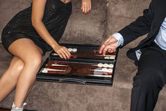 Backgammon player. A sexy woman and a man playing backgammon Royalty Free Stock Photo