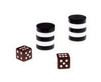 Backgammon. Stacked backgammon black and white pieces and dice isolated on white background Royalty Free Stock Photography