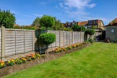 Backgarden-Blumenbeet mit Zaun Stockfotos