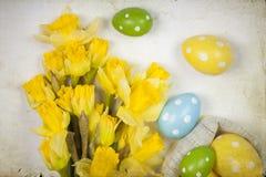 Backgound de Pâques outre des oeufs peints et des fleurs jaunes Photos libres de droits