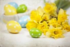 Backgound de Pâques outre des oeufs peints et des fleurs jaunes Photographie stock