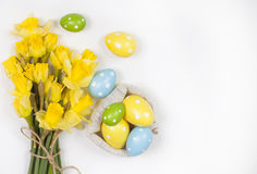 Backgound de Pâques outre des oeufs peints et des fleurs jaunes Photo libre de droits