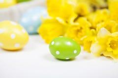 Backgound de Pâques outre des oeufs peints et des fleurs jaunes Image libre de droits