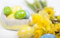 Backgound de Pâques outre des oeufs peints et des fleurs jaunes Photos stock